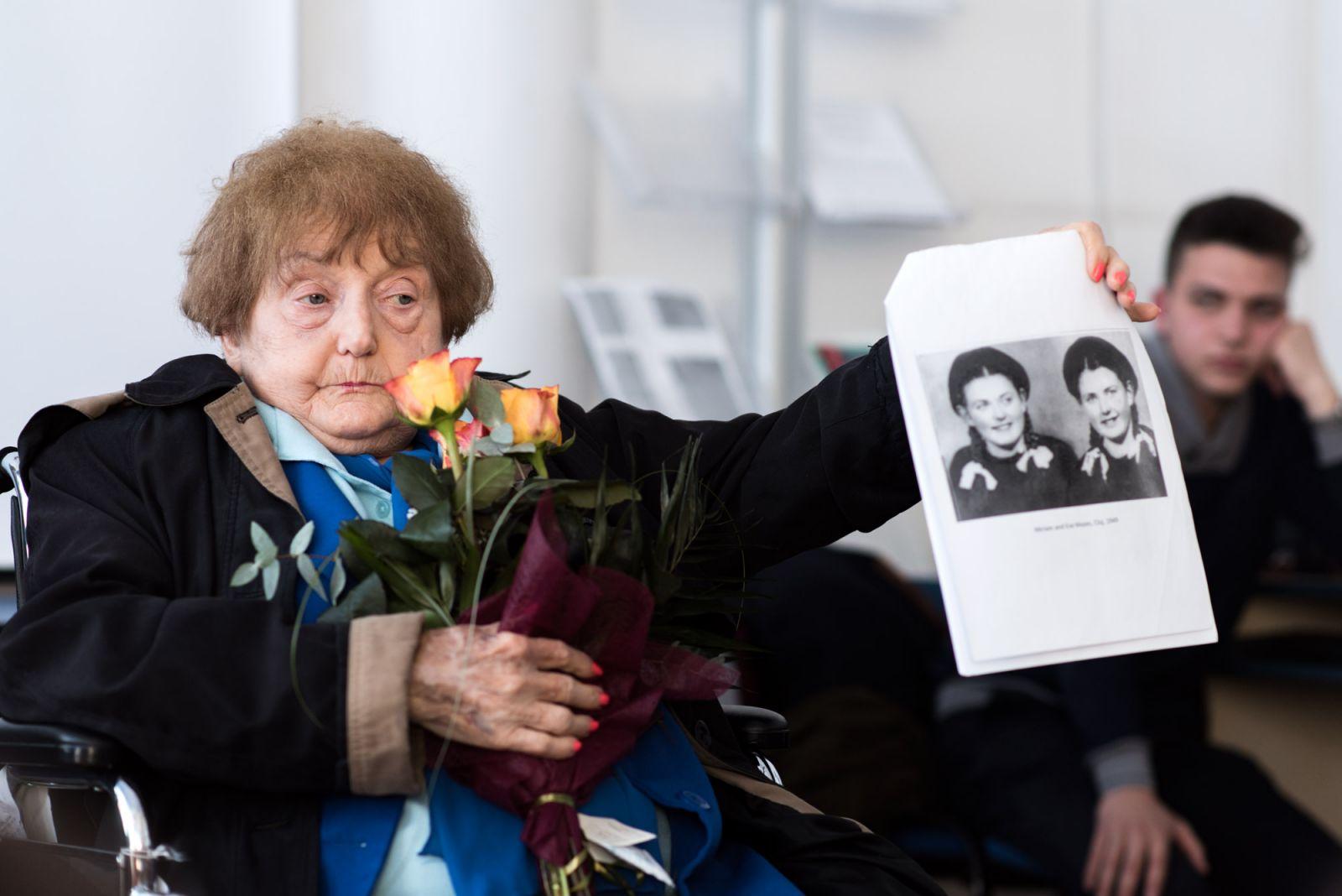 Eva Kor a kolozsvári licistáknak megmutatja, hogyan nézett ki ő meg ikertestvére, amikor 1948-ban ugyanabba az iskolába jártak | Forrás: pressone