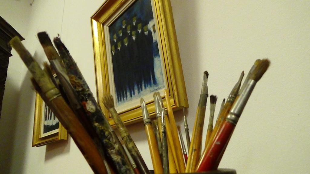 Györkös ecsetjei háttérben az egyik festményével   Fotó: a szerző felvétele